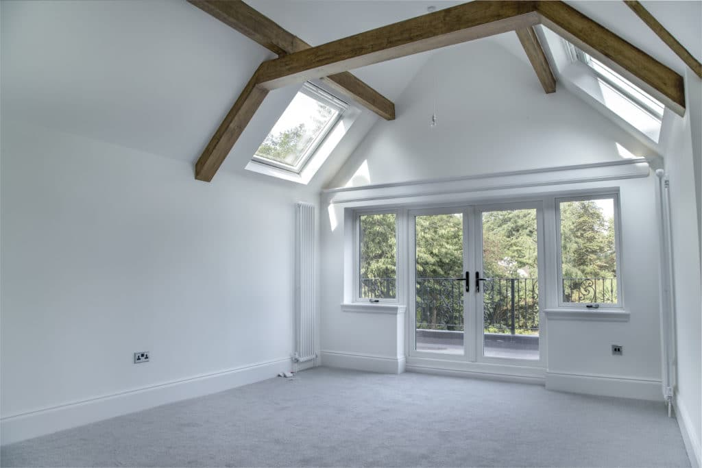 Empty room with wooden beams and a grey carpet